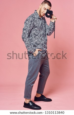 Elegant man in black and white shirt with masquerade mask in his hands on a pink background
