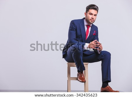 elegant man in business suit sitting in studio with palms touching while resting his leg on chair #342435623
