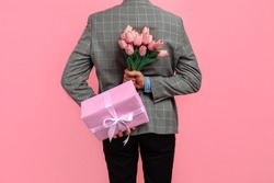 Elegant man in suit holding a festive pink box and a bouquet of flowers behind his back on a pink background, a gift for womens day, Valentine's Day concept