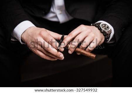 elegant man wearing black suit and white shirt cut Cuban cigar indoor shot, closeup #327549932