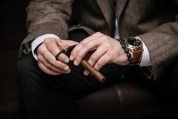 elegant man wearing suit and white shirt cut Cuban cigar indoor shot, closeup, selective focus