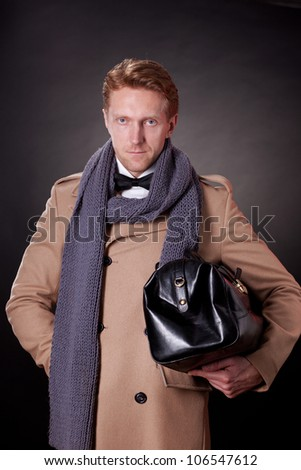 elegant man with a hand bag wearing a beige coat, scarf and a bow