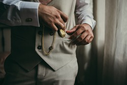 Elegant man with suit. Closeup groom hands holding a pocket watch.