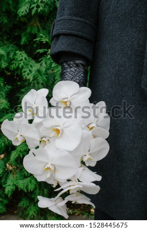 Elegant man with wedding bouquet made of white chic  phalaenopsis orchid in his hand. Wearing luxury black coat and leather gloves