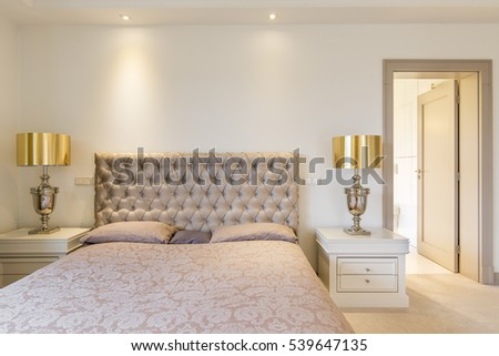 Elegant master bedroom with double bed with quilted headboard #539647135