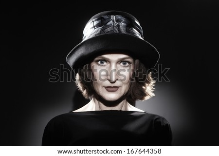 Elegant mature woman in hat fashion portrait. Beautiful senior woman portrait 60 years old on black