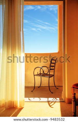 Elegant metal chair on sunny balcony, blue sky behind.