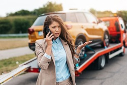 Elegant middle age business woman calling someone while towing service helping her on the road. Roadside assistance concept.