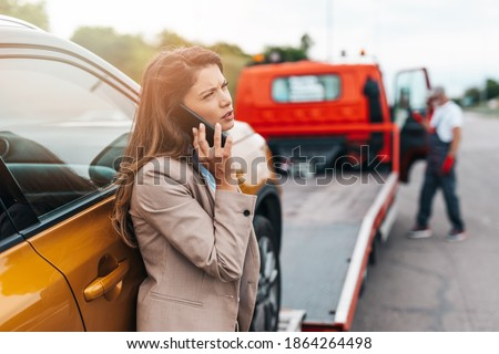 Elegant middle age business woman calling someone while towing service helping her on the road. Roadside assistance concept. Stock photo ©