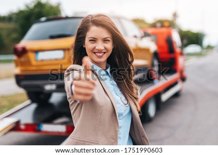 Elegant middle age business woman is happy and satisfied with fast and reliable towing service for help on the road. She showing thumb up. Roadside assistance concept.
