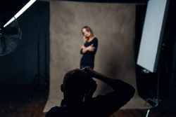 elegant model in black clothes posing for photographers in a dark room