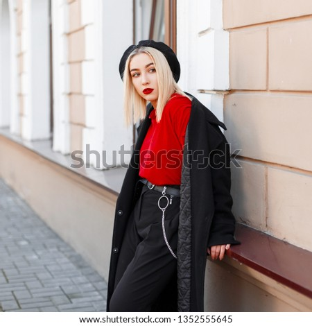 Elegant modern young woman in a beret in a red shirt with a fashionable long coat in stylish trousers near a vintage building in autumn day. Pretty pretty girl on a walk. Retro style.