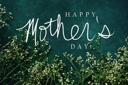 Elegant mother's day background with dainty flowers on green color backdrop.