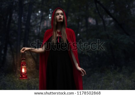 elegant mystic girl in red cloak with kerosene lamp walking in dark woods  #1178502868