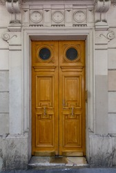 Elegant old double door entrance of building in Paris France. Vintage wooden doorway and stucco fretwork wall of ancient stone house with round medallions. Ornate carving wood door with round windows