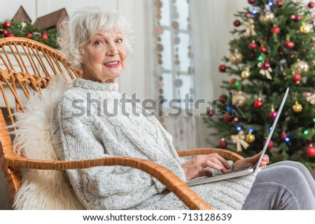 Elegant old female is working on computer with smile #713128639