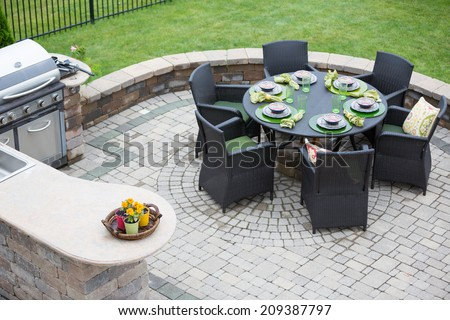 Elegant outdoor living space on a paved brick patio with a summer kitchen and barbecue and a table laid with formal place settings for dinner, high angle view