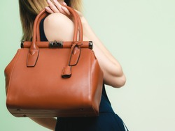 Elegant outfit. Closeup of brown leather bag handbag in hand of stylish woman fashionable girl on green. Female fashion.