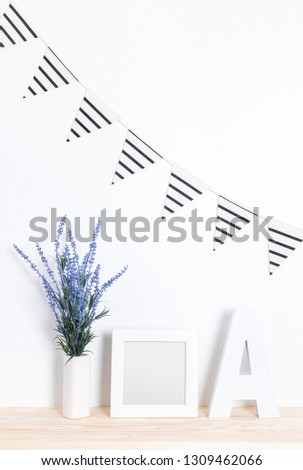 Elegant party interior design in white and blue tones. Bunting flags, lavender, picture frame and wooden letter A.