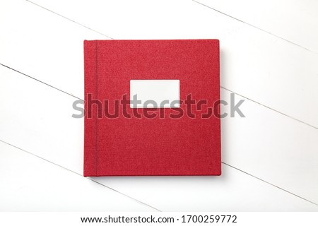 Elegant photobook with red linen cover and metal nameplate. Wedding photobook. Wedding photo album Сток-фото ©