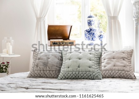 Elegant pillows on bed in bright feminine bedroom interior with record player at window. Real photo