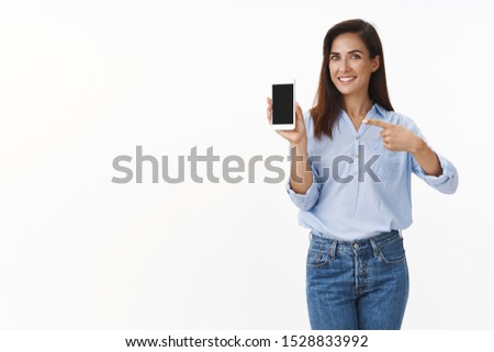 Elegant pleased good-looking cheerful adult lady promote smartphone, hold mobile phone, pointing gadget screen recommend use app, show summer vacation pics display, smiling happily