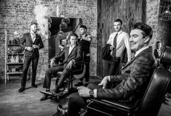 Elegant positive mens pose in barbershop. Black-white photo.