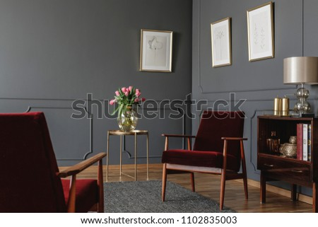 Elegant psychologist's office interior with two red armchairs facing each other between a golden table with flowers and vintage, wooden cabinet. Real photo