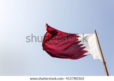 Elegant Qatar flag flying in the sky on a bright sunny day