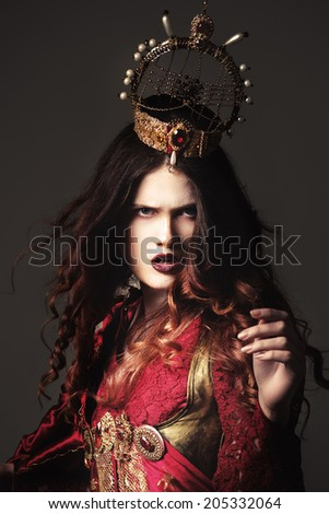 Elegant queen female face with red lips and black eye makeup. evil Queen