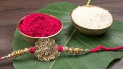 Elegant Rakhi on green leaf, Rice Grains and Kumkum. A traditional Indian wrist band which is a symbol of love between Brothers and Sisters. Indian festival.