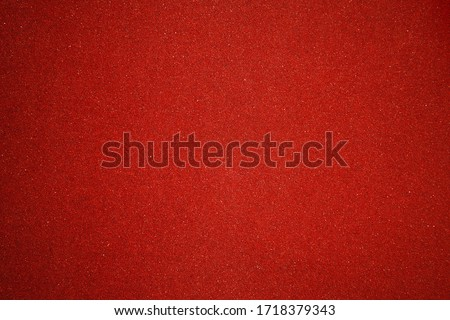 Elegant red canvas background with vignette and small dots. Scarlet backdrop for festive decoration and internet design. texture of sandpaper Foto d'archivio ©