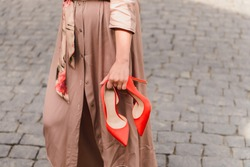 Elegant red high heels shoes in woman hands. Girl wearing beige trench coat standing on a stony pavement, holding her trendy, fashion footwear in hands