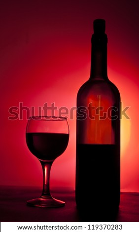 Elegant red wine glass and a wine bottle in black and red gradient background