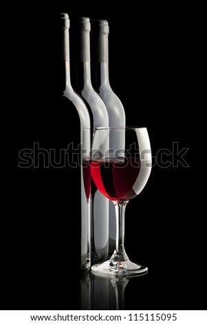 Elegant red wine glass and a wine bottles in black background