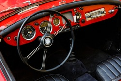 Elegant retro car, vintage cabriolet and red dashboard close-up, behind the big black wheel of such a classy automobile you want to press the gas and go on a sunny summer day in South of France