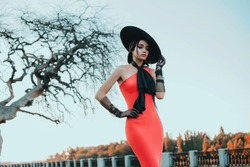Elegant retro lady in a long red evening glamour dress. Young stylish trendy woman. black hat with wide brim and high tulle gloves. bow at  neck. Adult woman fashion model stands on old city street.