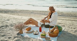 Elegant romantic couple having picnic at the beach, embracing and lying blanket. Romance, dating and love concep