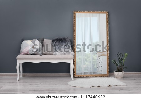 Elegant room interior with large mirror and bench #1117440632