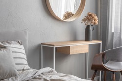 Elegant round mirror in wooden frame above fancy console table with flowers in vase in trendy bedroom interior with beige vase