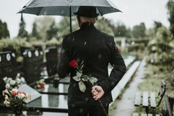 Elegant sad elderly man standing on the rain with umbrella and grieves at the grave of a loved person