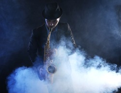 Elegant saxophonist plays jazz on dark background in a smoke
