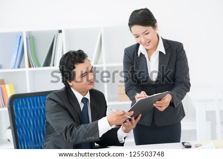 Elegant secretary bringing some documents for signature to her boss