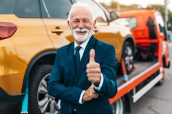 Elegant senior businesman is happy and satisfied with fast and reliable towing service for help on the road. He is standing in front of wrecker with arms crossed. Roadside assistance concept.