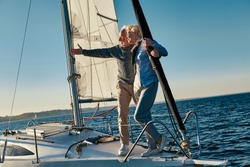 Elegant senior man pointing at the horizon while standing with his wife on the side of a sail boat or yacht deck floating in a calm blue sea, enjoying amazing view