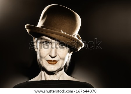 Elegant senior woman in hat fashion portrait. Pretty mature lady 60 years old in retro style