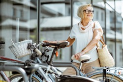 Elegant senior woman parking a bicycle near the modern building outdoors. Concept of an active lifestyle on retirement age
