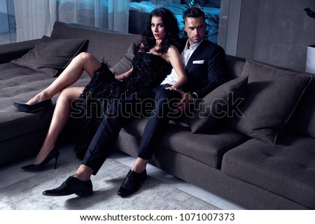 Elegant, sensual couple sitting on the couch #1071007373