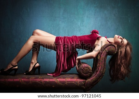 elegant sensual young woman in red dress on recliner indoor shot