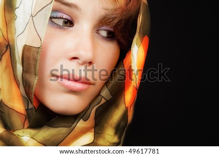 Elegant sensual young woman with colorful vail over black